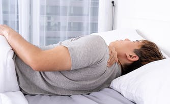 person with herniated disc sleeping in bed