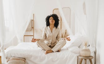person sitting on top of bed meditating