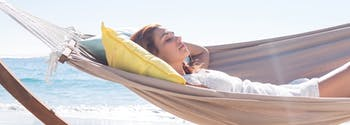 person sleeping in hammock on beach