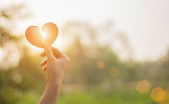 grieving person holding a broken heart