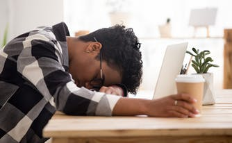 person with sleep disorder sleeping with head down on desk