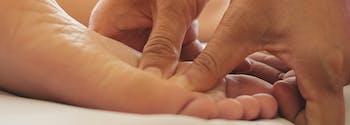 hands massaging foot during reflexology massage