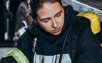 tired firefighter sitting against firetruck