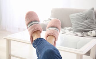 image of person's feet in slippers at home