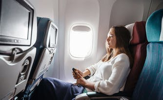 best and worst cures for jet lag - image of person sitting on airplane