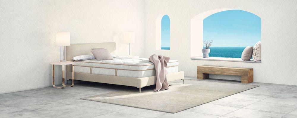 saatva latex hybrid mattress in bedroom with pink blanket hanging off edge of bed