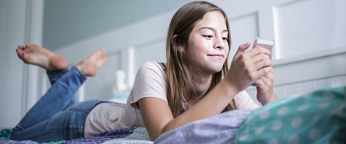 tween looking at phone in bed