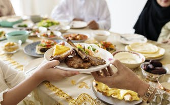 Family passing a plate of meat as part of ramadan feast