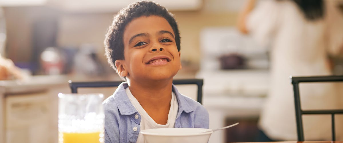 child eating breakfast before school in the morning