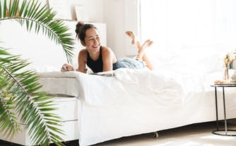 person lying on cooling sheets in bed