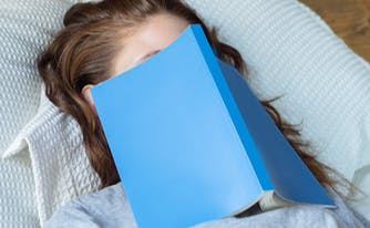 image of woman with book over her face - sleep learning