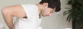 image of man with back pain in bed