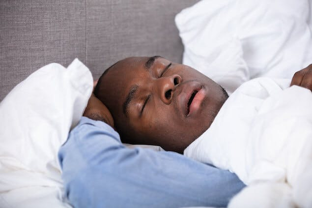 person snoring in bed, which can lead to a tension headache