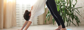 best way to sleep with back pain - image of woman doing downward dog
