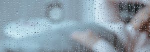 person sleeping in bed with rain outside