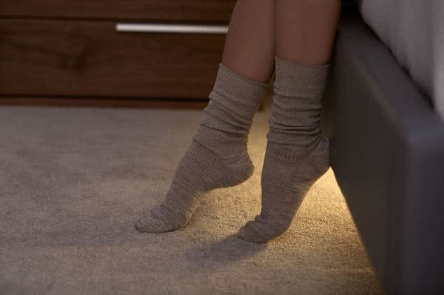 person's feet getting out of bed with lights underneath adjustable base