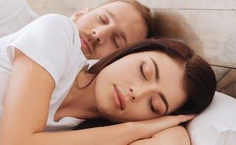 image of couple sleeping in bed - how to break in a memory foam mattress