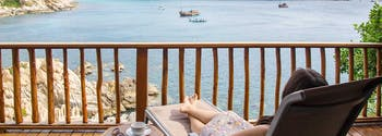 image of woman sleeping by beach while traveling