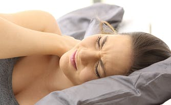 best pillow for back and neck pain - image of woman with neck pain sleeping on pillow