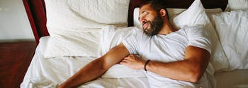 best sleeping position for back pain - image of man sleeping on back
