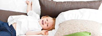 image of child laughing in bed