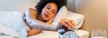 sleep myths - person hitting alarm clock in bed