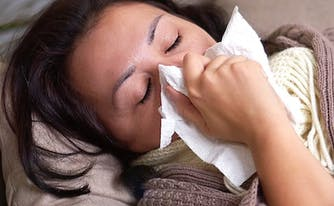 person with covid-19 lying on couch, wrapped in blanket, and blowing nose