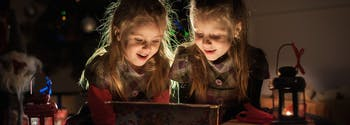 image of two children opening holiday gifts