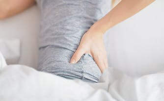 image of a woman touching back in pain - can a mattress cause back pain