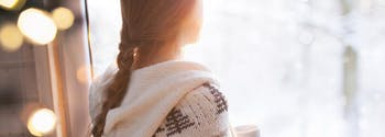 image of woman with seasonal affective disorder looking out window