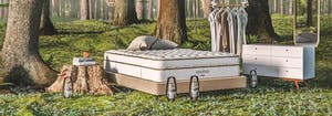 mattress, dresser, and clothing rack outside in forest to symbolize the concept of friluftsliv
