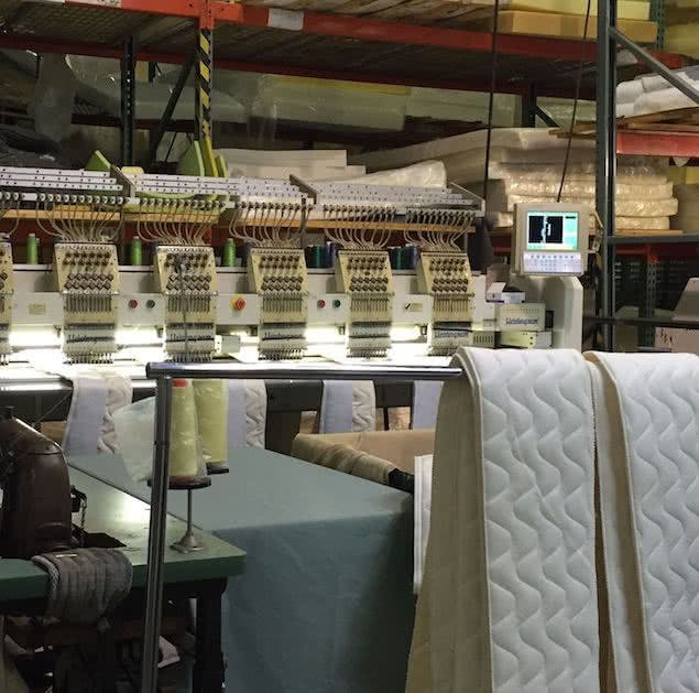 saatva mattress factory with sewing station and fabric panels