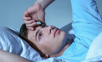 image of man with anxiety awake in bed