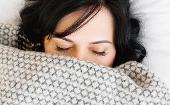 image of woman wrapped in weighted blanket