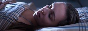 person sleeping in dark bedroom