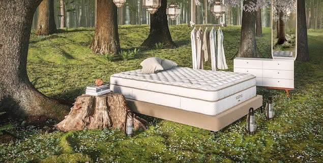 friluftsliv style bedroom with mattress outside in forest next to clothing rack