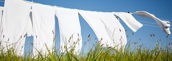 how to clean bedding - image of sheets drying on clothing line