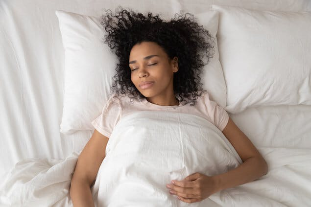 how to sleep with lower back pain - person lying on back