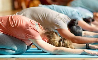 image of people in yoga class doing child's pose