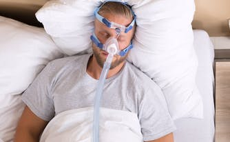 image of man with sleep apnea wearing a cpap mask in bed