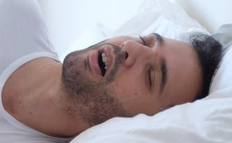 image of man snoring in bed