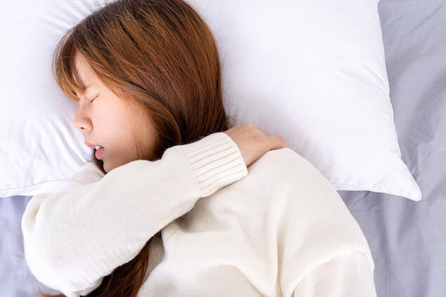 person with neck pain sleeping on pillow that needs to be replaced