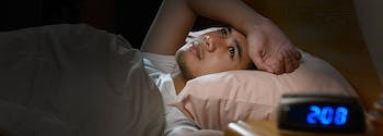 image of man with insomnia staring at ceiling in bed