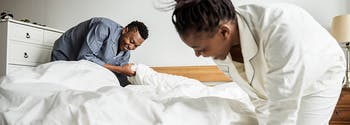 image of woman making bed in the morning
