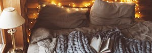 cottagecore themed bedroom with twinkling lights and cozy bed sheets