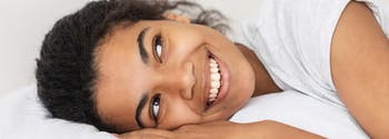 person happy in bed for world sleep day