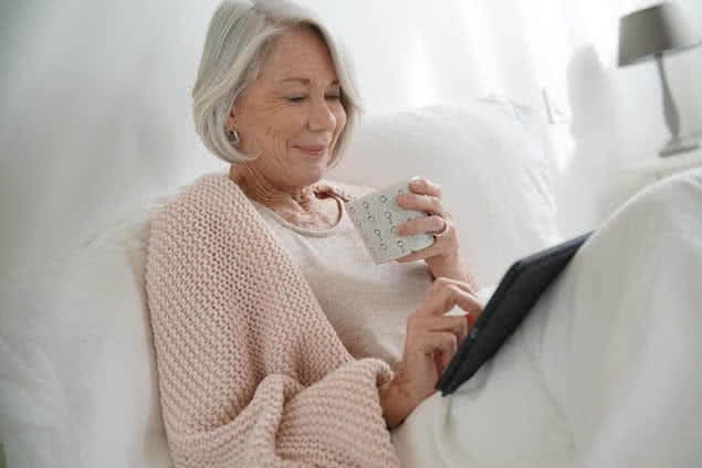 senior person lying in bed reading book with cup of coffee