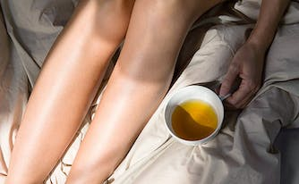image of woman drinking tea in bed - natural sleep supplements