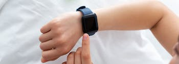 person with sleep tracker on wrist in bed