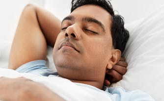 best hybrid mattress for back sleeper - image of person sleeping on back